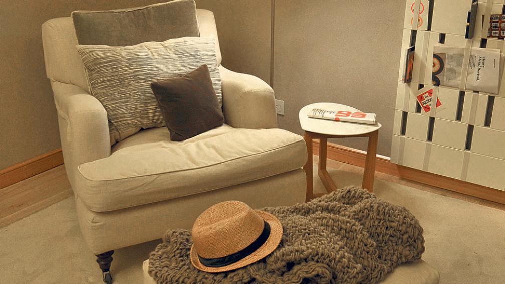 Imagen de confort total, en tonos cálidos con almohadones engamados, armando el rincón junto a un apoyapie.