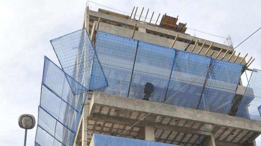 Imprudencia. En el 5° piso, un muchacho dormita. Apoya la espalda sobre un rejilla, en General Paz (Martín Baéz/LaVoz).
