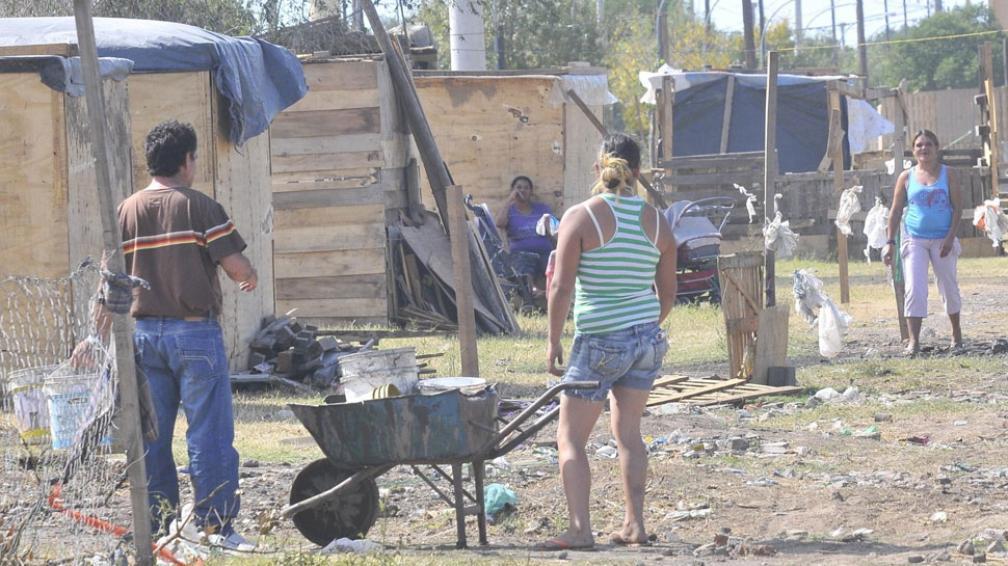 Sin agua ni luz. Algunos reciben la luz por cables que tiran desde viviendas vecinas de Ciudad Evita. Desde ahí acarrean el agua en tarros (Ramiro Pereyra / La Voz).