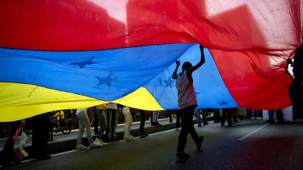 Embanderados. Empleados estatales marcharon en apoyo a Maduro. Estudiantes volvieron a protestar (AP).