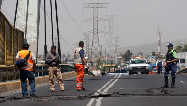 MÉXICO. Trabajadores inspeccionan parte de la rotura de un puente de Ciudad de México tras el sismo (AP).