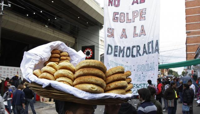 Rechazo visible. Frente a la sede de la TV pública en Asunción, los chipás y un cartel de repudio al golpe (AP).