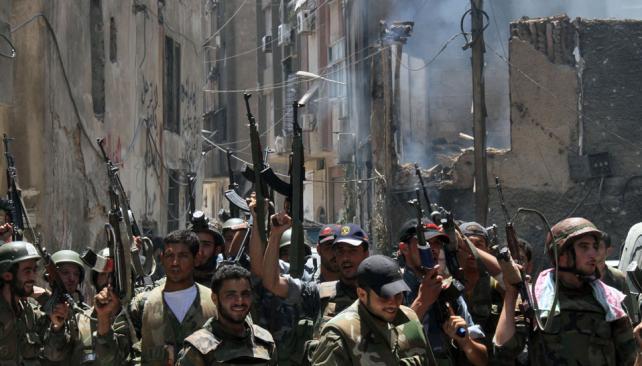 Festejo. Militares del régimen celebran la recuperación del barrio de Midan, en la parte sur de Damasco (AP).