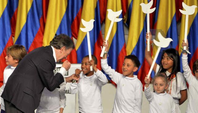 Símbolos. En la noche de su victoria en el balotaje, niños con palomas de la paz enmarcaron el discurso de Santos (AP).
