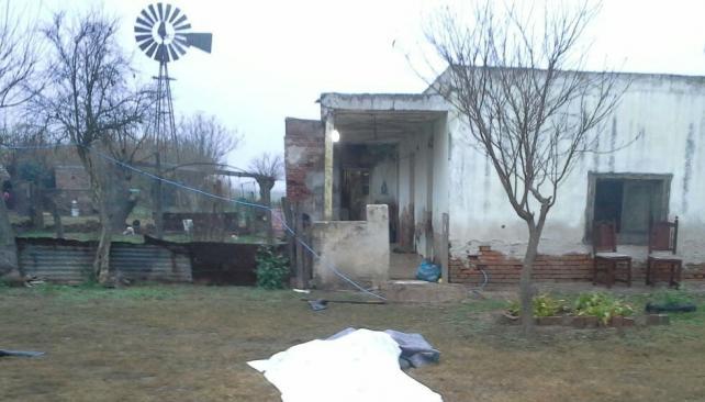 Tragedia. Debajo de una sábana y de una lona yacen los cuerpos de la chica y del hombre. Atrás, la vivienda rural.