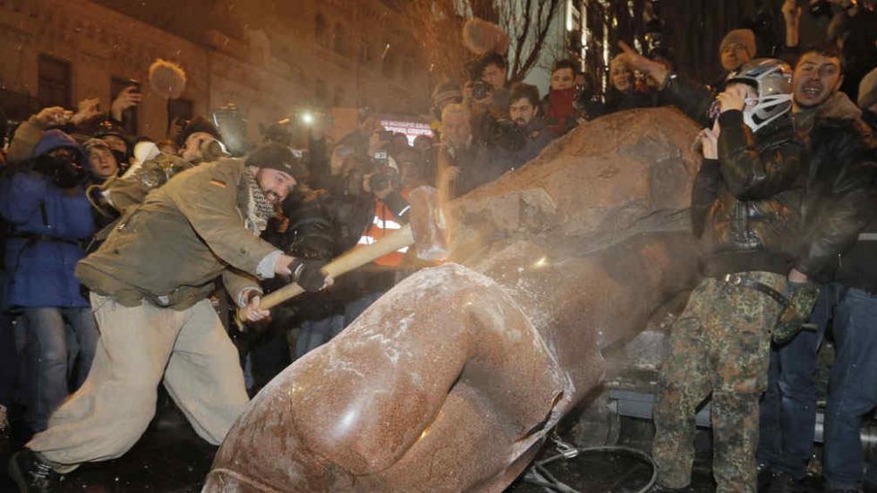 Antes y después. A la izquierda, Sigismondi, ante la estatua de Lenin en Kiev.  A la derecha, el ícono  ruso es destruido por los manifestantes proeuropeos (AP).