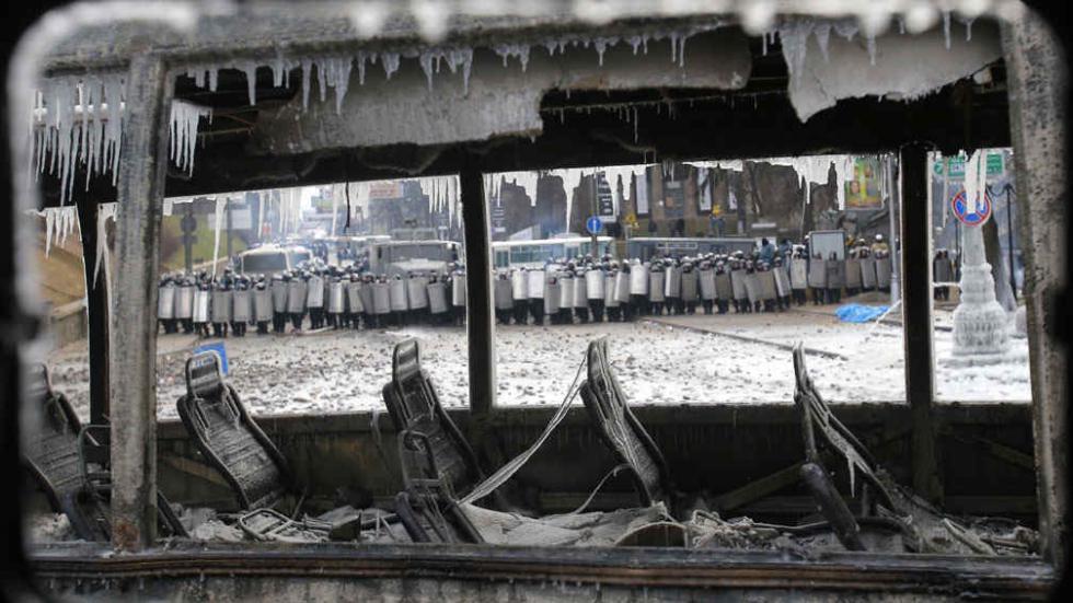 El día después. Luego de  una noche de incidentes y violencia en  el centro de Kiev, los manifestantes usaron ómnibus incendiados como barricadas. Atrás, la  policía ucraniana. Fue el 20 de enero (AP).